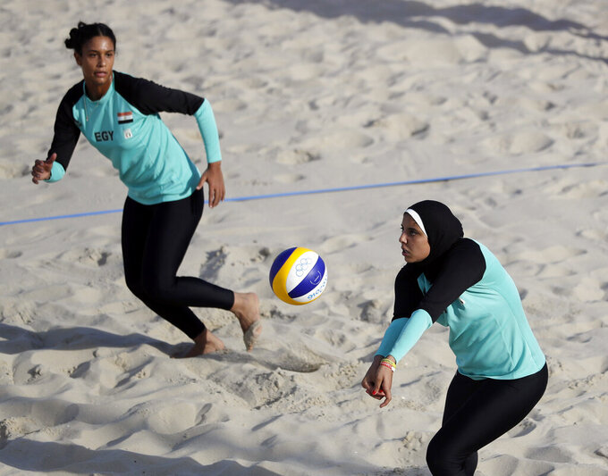 FILE - In this Aug. 11, 2016, file photo, Egypt's Doaa Elghobashy, right, sets up for teammate Nada Meawad against Canada during a women's beach volleyball match at the 2016 Summer Olympics in Rio de Janeiro, Brazil. Most of the women playing beach volleyball at the Olympics wear bikinis as their uniform, but it's not required. The rules allow women different options, including long and short pants and more conservative attire for those whose religious beliefs require it. (AP Photo/Marcio Jose Sanchez, File)