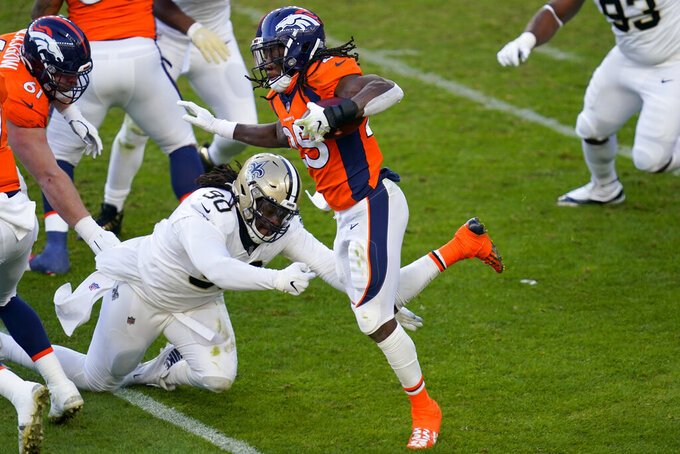 Denver Broncos running back Melvin Gordon (25) eludes the reach of New Orleans Saints defensive tackle Malcom Brown (90) during the second half of an NFL football game, Sunday, Nov. 29, 2020, in Denver. (AP Photo/David Zalubowski)