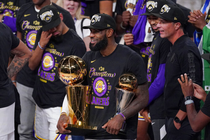 FILE - In this Oct. 11, 2020, file photo, Los Angeles Lakers' LeBron James (23) holds the trophies as he celebrates with his teammates after the Lakers defeated the Miami Heat 106-93 in Game 6 of basketball's NBA Finals in Lake Buena Vista, Fla. James was announced Saturday, Dec. 26,  as the winner of The Associated Press' Male Athlete of the Year award for a record-tying fourth time.  (AP Photo/Mark J. Terrill, File)