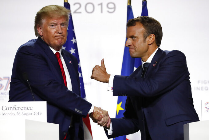 FILE - In this Aug. 26, 2019, file photo, French President Emmanuel Macron and U.S President Donald Trump shake hands during the final press conference during the G7 summit in Biarritz, southwestern France. With a year to go to the presidential vote, French President Emmanuel Macron is getting ready for a potential re-election bid by prioritizing reviving the economy and saving jobs. The country is slowly stepping out of its partial lockdown. Macron's ability to meet the challenge will be key _ as France is among countries worst hit by the pandemic in the world, with over 105,000 virus-related deaths. (AP Photo/Francois Mori, File)