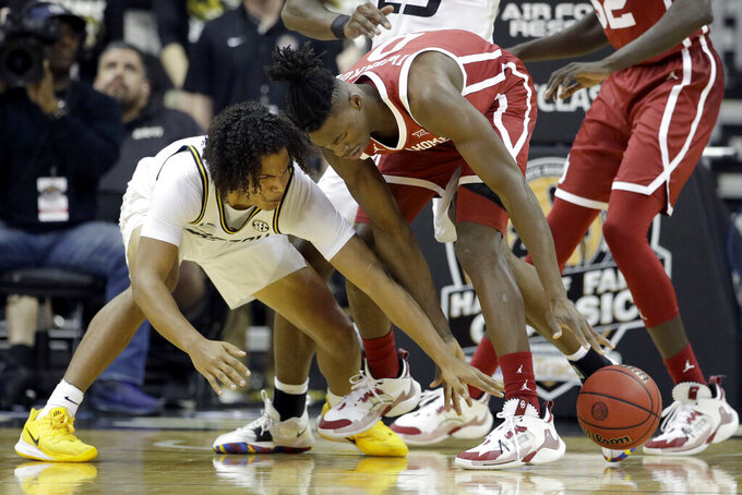 Missouri guard Dru Smith, left, and Oklahoma forward Victor Iwuakor (0) chase a loose ball during the first half of an NCAA college basketball game, Tuesday, Nov. 26, 2019, in Kansas City, Mo. (AP Photo/Charlie Riedel)
