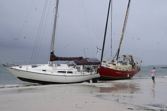 Boats sit on the beach in the aftermath of Tropical Storm Eta, Thursday, Nov. 12, 2020, in Gulfport, Fla. Eta dumped torrents of blustery rain on Florida's west coast as it slogged over the state before making landfall near Cedar Key, Fla. (AP Photo/Lynne Sladky)