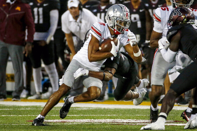 Ohio State wide receiver Chris Olave (2) catches a pass as Minnesota defensive back Jordan Howden, front right, tries to tackle him in the first quarter of an NCAA college football game Thursday, Sept. 2, 2021, in Minneapolis. (AP Photo/Bruce Kluckhohn)