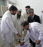 FILE-In this Aug. 28, 2008, photo, Afghan hospital officials and the Japanese doctor Tetsu Nakamura, second right in black suit, looks on the Japanese aid worker Kazuya Ito, at the hospital in Jalalabad city the provincial capital of Nangarhar province. The Japanese physician and aid worker in eastern Afghanistan died of his wounds after an attack Wednesday, Dec. 4, 2019, that also killed five Afghans, including the doctor's bodyguards, the driver and a passenger, a hospital spokesman said. (AP Photo/Rahmat Gul, File)