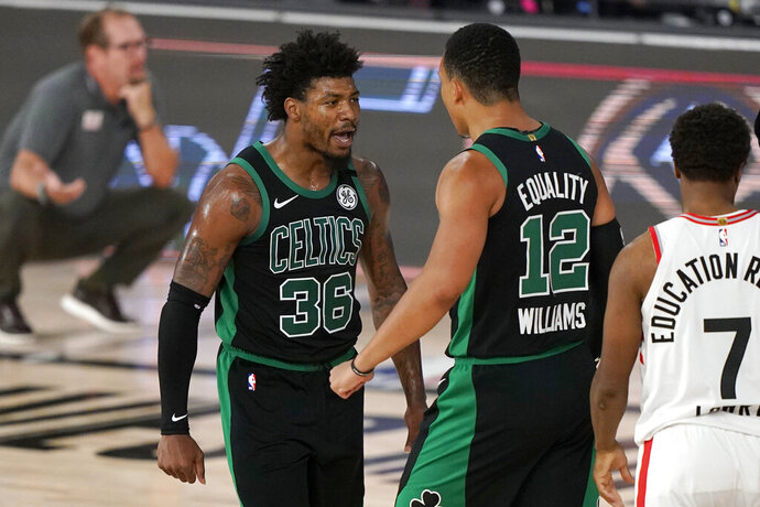 Boston Celtics' Marcus Smart (36) celebrates with Grant Williams (12) after sinking a basket and drawing a foul in the second half of an NBA conference semifinal playoff basketball game as Toronto Raptors' Kyle Lowry looks on Tuesday, Sept. 1, 2020, in Lake Buena Vista, Fla. (AP Photo/Mark J. Terrill)