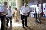 Cuba's President Miguel Diaz-Canel cuts the ceremonial ribbon to inaugurate the annual International Trade Fair in Havana, Cuba, Monday, Nov. 4, 2019. (AP Photo/Ismael Francisco)