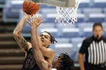 North Carolina Central forward Justin Whatley (13) shoots over North Carolina forward Armando Bacot during the second half of an NCAA college basketball game in Chapel Hill, N.C., Saturday, Dec. 12, 2020. (AP Photo/Gerry Broome)