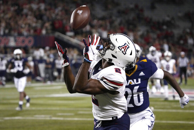Arizona wide receiver Boobie Curry scores a touchdown behind Northern Arizona defensive back Colby Humphrey (26) during the first half of an NCAA college football game, Saturday, Sept. 18, 2021, in Tucson, Ariz. (AP Photo/Rick Scuteri)