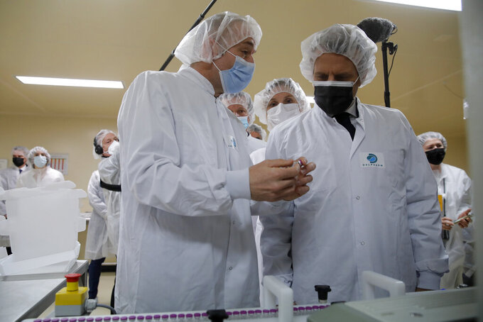 French President Emmanuel Macron, right, listen to plant manager Wladimir Guitel, as he visits the Delpharm plant in Saint-Remy-sur-Avre, west of Paris, Friday, April 9, 2021 in Paris. The Delpharm plant started bottling Pfizer vaccines this week as France tries to make its mark on global vaccine production, and speed up vaccinations of French people amid a new virus surge. (AP Photo/Christophe Ena, Pool)
