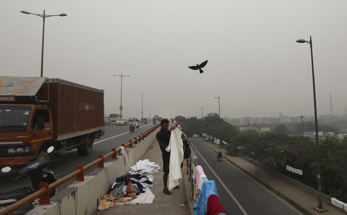 A washerman collects the clothes spread for drying at an over-bridge as city is seen enveloped in thick layer of smog in New Delhi, India, Thursday, Nov. 14, 2019. Schools in India's capital have been shut for Thursday and Friday after air quality plunged to a severe category for the third consecutive day, enveloping New Delhi in a thick gray haze of noxious air. (AP Photo/Manish Swarup)