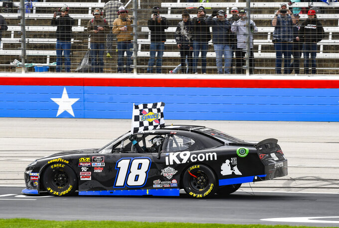Driver Kyle Busch celebrates with the checkered flag after winning a NASCAR auto race at Texas Motor Speedway, Saturday, March 30, 2019, in Fort Worth, Texas. (AP Photo/Randy Holt)