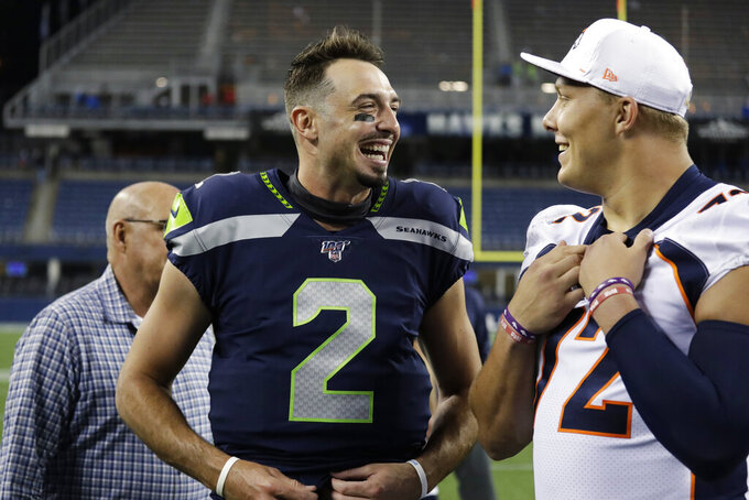 Seattle Seahawks quarterback Paxton Lynch, left, talks with Denver Broncos offensive tackle Garett Bolles after an NFL football preseason game Thursday, Aug. 8, 2019, in Seattle. The Seahawks won 22-14. (AP Photo/Elaine Thompson)