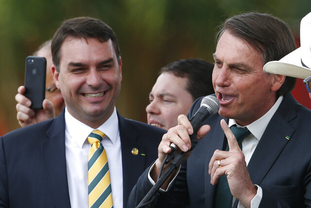 FILE - This Nov. 21, 2019 file photo shows Sen. Flavio Bolsonaro, left, with his father Brazilian President Jair Bolsonaro at the launch of his father's new political party Alliance for Brazil in Brasilia, Brazil. Public prosecutors in Rio de Janeiro state have indicted Sen. Flávio Bolsonaro for allegedly commanding a criminal organization and laundering money when he was a state lawmaker between 2007 and 2018, according to a statement the public prosecutors' office posted to its website on Wednesday, Nov. 4, 2020. (AP Photo/Eraldo Peres, File)
