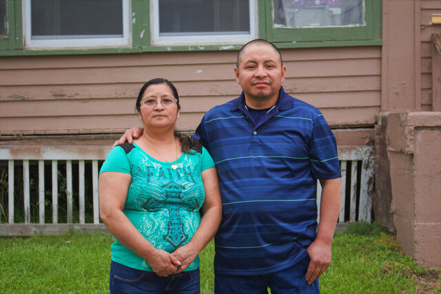 In this photo provided by Cristobal Francisquez, his parents Paulina and Marcos Francisco pose for a photo in front of their house in Sioux City, Iowa, Monday, May 25, 2020. They bought the home after years of working in a meatpacking plant and other food processing jobs. (Cristobal Francisquez via AP)
