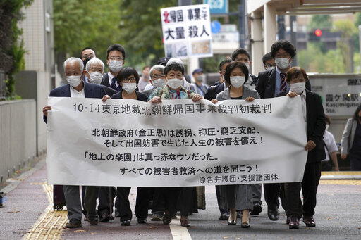 """Plaintiffs and their supporters walk toward the Tokyo District Court Thursday, Oct. 14, 2021, in Tokyo. The court is hearing five ethnic Korean residents of Japan and a Japanese national demanding the North Korean government pay compensation over their human rights abuses in that country after joining a resettlement program there that promised a """"paradise on Earth,"""" but without the presence of a defendant - the North's leader. The banner reads: """"Oct. 14 Tokyo District Court the North Korea """"Paradise on Earth"""" campaign first trial. (AP Photo/Eugene Hoshiko)"""