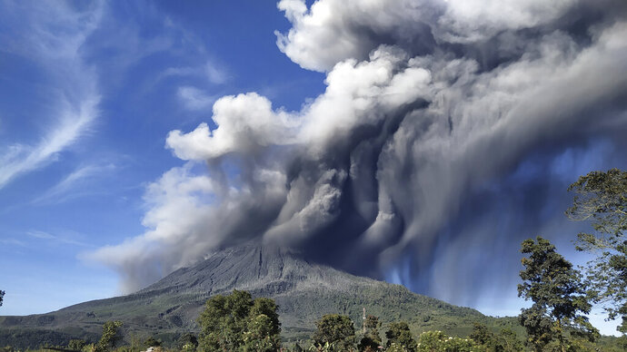 Mount Sinabung spews volcanic materials during an eruption, in Karo, North Sumatra, Indonesia, Sunday, Aug. 23, 2020. Sinabung is among more than 120 active volcanoes in Indonesia, which is prone to seismic upheaval due to its location on the Pacific