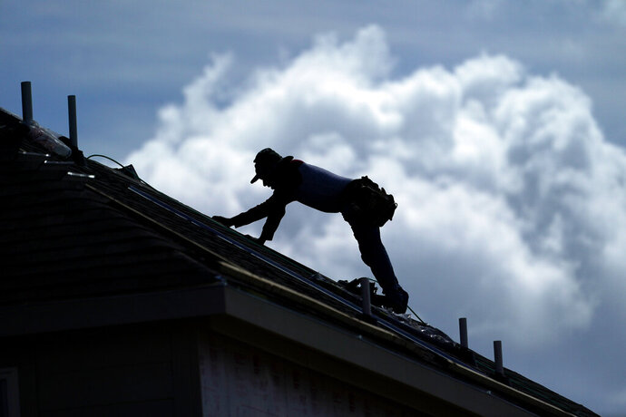 A roofer works on a new home under construction Thursday, July 18, 2019, in Houston. A heat wave is expected to send temperatures soaring close to 100 degrees through the weekend across much of the country. The National Weather Service estimates that more than 100 heat records will fall on Saturday, August 17. Most will not be the scorching daily highs, but for lack of cooling at night, something called nighttime lows. Those lows will be record highs. (AP Photo/David J. Phillip)