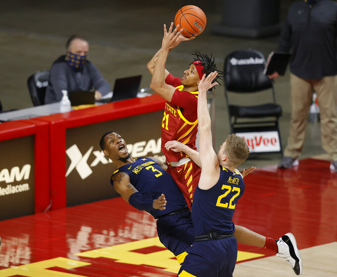 Iowa State guard Jaden Walker, center is charged with an offensive foul as he drives against West Virginia forward Gabe Osabuohien, left, and West Virginia guard Sean McNeil, right, during the first half of an NCAA college basketball game, Tuesday, Feb. 2, 2021, in Ames, Iowa. (AP Photo/Matthew Putney)