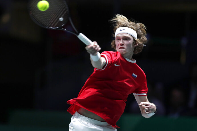 Russia's Andrey Rublev returns the ball to Spain's Roberto Bautista Agut during their Davis Cup tennis match in Madrid, Spain, Tuesday, Nov. 19, 2019. (AP Photo/Manu Fernandez)