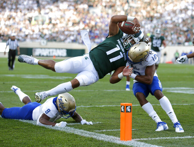 Michigan State running back Connor Heyward (11) goes over Tulsa's Brandon Johnson, left, and collides with Manny Bunch (10) as he scores on a pass reception during the first quarter of an NCAA college football game, Friday, Aug. 30, 2019, in East Lansing, Mich. (AP Photo/Al Goldis)