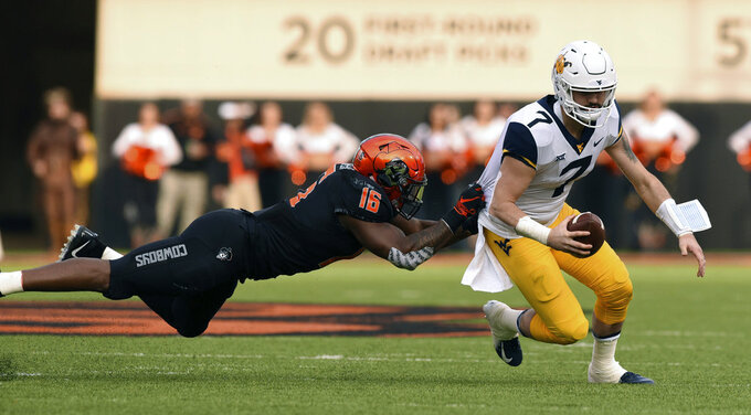 Oklahoma State linebacker Devin Harper (16) grabs the jersey of West Virginia quarterback Will Grier (7) during the first half of an NCAA college football game in Stillwater, Okla., Saturday, Nov. 17, 2018. Grier had 2 touchdowns in the 41-45 loss to Oklahoma State. (AP Photo/Brody Schmidt)