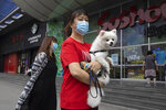 A woman wearing a mask to curb the spread of the coronavirus holds her dog as they pass by a mall in Beijing on Monday, June 29, 2020. Even as the world surpassed two sobering coronavirus milestones Sunday -- 500,000 confirmed deaths, 10 million confirmed cases -- and hit another high mark for daily new infections, China on Monday reported a further decline in new confirmed cases. (AP Photo/Ng Han Guan)