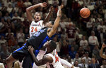Duke center Marques Bolden (20) is fouled as Virginia Tech's Kerry Blackshear Jr. (24) and Ty Outlaw (42) defend during the first half of an NCAA college basketball game in Blacksburg, Va., Tuesday, Feb. 26, 2019. (AP Photo/Lee Luther Jr.)