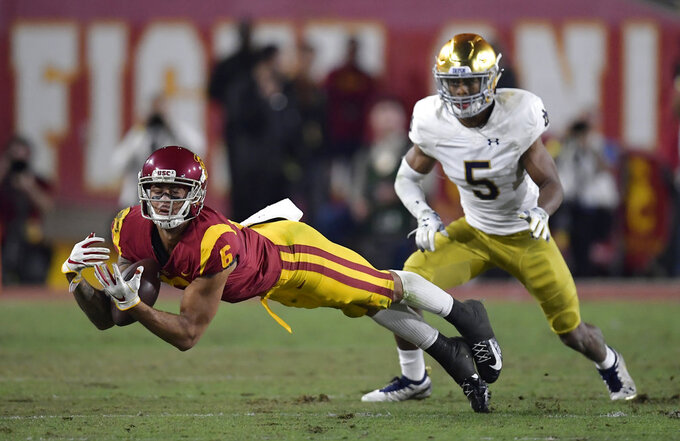 Southern California wide receiver Michael Pittman Jr., left, attempts to catch a pass while under pressure from Notre Dame cornerback Troy Pride Jr. during the first half of an NCAA college football game Saturday, Nov. 24, 2018, in Los Angeles. The play was initially ruled a catch but the call was overturned after review. (AP Photo/Mark J. Terrill)