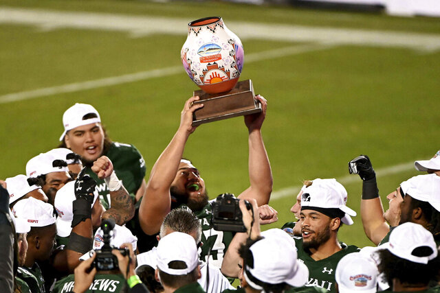 Hawaii linebacker Darius Muasau (53) holds up the trophy after the team's 28-14 win over Houston in the New Mexico Bowl NCAA college football game in Frisco, Texas, Thursday, Dec. 24, 2020. (AP Photo/Matt Strasen)