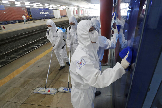 South Korean soldiers wearing protective gears disinfect as a precaution against the new coronavirus at a train station in Daejeon, South Korea, Thursday, June 25, 2020. (Kim Jun-beom/Yonhap via AP)