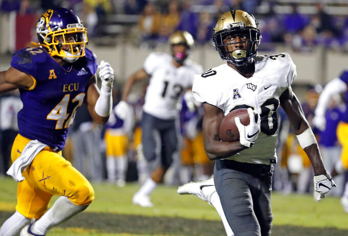 Central Florida's Alex Swenson (30) runs away from East Carolina's Devon Sutton (42) during the second half of an NCAA college football game in Greenville, N.C., Saturday, Oct. 20, 2018. UCF won 37-10. (AP Photo/Karl B DeBlaker)
