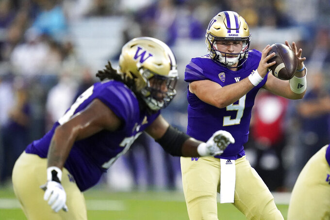 Washington quarterback Dylan Morris (9) takes a snap against California during the first half of an NCAA college football game, Saturday, Sept. 25, 2021, in Seattle. (AP Photo/Elaine Thompson)