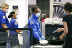 FILE - In this May 18, 2020 file photo TSA officers wear protective masks at a security screening area at Seattle-Tacoma International Airport in SeaTac, Wash. Federal safety officials are investigating people who took part in last week's riot at the U.S. Capitol to decide whether they belong on the federal no-fly list. The move is one of several that officials outlined Friday, Jan. 15, 2021. (AP Photo/Elaine Thompson, File)