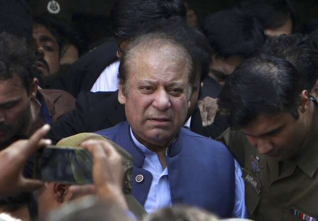 FILE - In this Oct. 8, 2018, file photo, former Pakistani Prime Minister Nawaz Sharif leaves after appearing in a court in Lahore, Pakistan. A Pakistani court on Tuesday Sept. 1, 2020 warned the country's ailing former Prime Minister Nawaz Sharif to return home by Sept. 10 to face a corruption hearing or risk being declared a fugitive from justice. Sharif has been in London since authorities last November released him so he could travel and seek medical treatment abroad. (AP Photo/K.M. Chaudary, File)