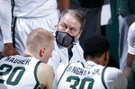 Michigan State coach Tom Izzo, center, talks to players during a timeout in the second half of an NCAA college basketball game against Indiana, Tuesday, March 2, 2021, in East Lansing, Mich. Michigan State won 64-58. (AP Photo/Al Goldis)