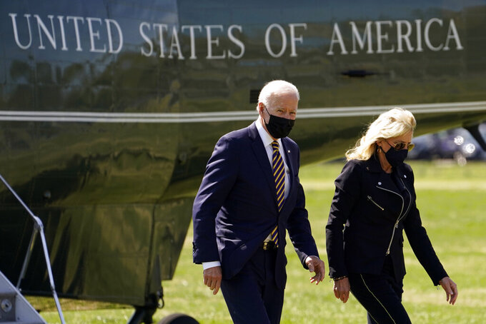 President Joe Biden walks from Marine One with first lady Jill Biden on the Ellipse on the National Mall after spending the weekend at Camp David, Monday, April 5, 2021, in Washington. (AP Photo/Evan Vucci)