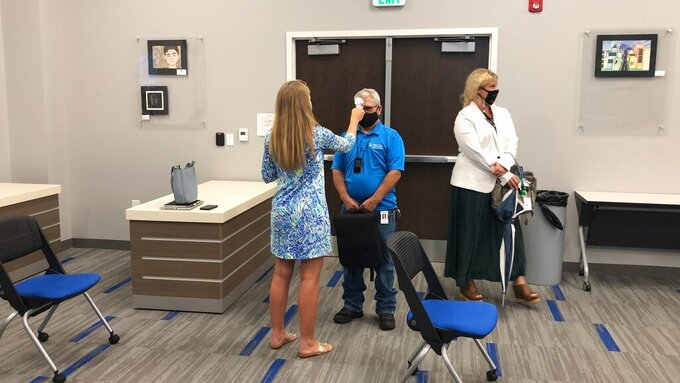 Rock Hill School Board member Terry Hutchinson gets his temperature checked before a meeting in Rock Hill, South Carolina, on Monday, Aug. 10, 2020. Like school boards across the nation, Rock Hill's board has had to answer the simple question when do children return to school with no easy or guaranteed safe answer.  (AP Photo/Jeffrey Collins)