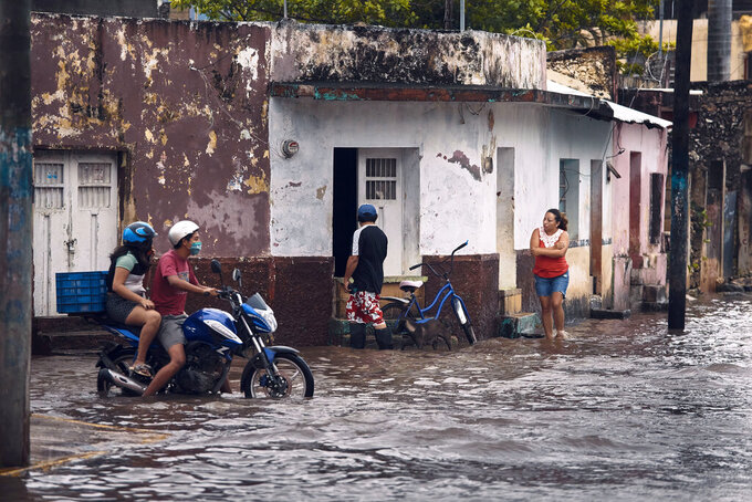 A couple rides a motorcycle along a flooded street after the passing of Hurricane Delta in Tizimin, Mexico, Wednesday, Oct. 7, 2020. Hurricane Delta made landfall Wednesday just south of the Mexican resort of Cancun as a Category 2 storm, downing trees and knocking out power to some resorts along the northeastern coast of the Yucatan Peninsula. (AP Photo/Andres Kudacki)