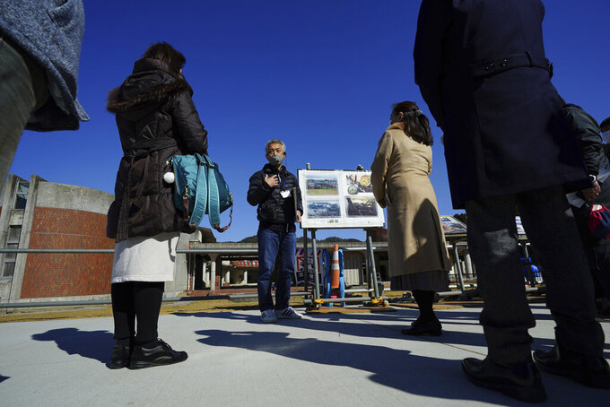 Noriyuki Suzuki, center, a volunteer who lost his 12-year-old daughter in a tsunami in 2011, tells his experience to a group of visitors in front of former Okawa Elementary School where 74 children from the elementary school lost their lives along with 10 teachers by the tsunami in Ishinomaki, Miyagi Prefecture, northern Japan, Saturday, March 6, 2021. Suzuki will take part in the torch relay for the upcoming Tokyo Olympics. (AP Photo/Eugene Hoshiko)