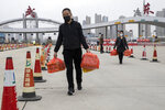 In this Thursday, April 2, 2020, photo, a man and woman carry eggs as they cross the expressway gate at the border into Wuhan city in central China's Hubei province. Millions of Chinese workers are streaming back to factories, shops and offices but many still face anti-coronavirus controls that add to their financial losses and aggravation. In Wuhan police require a health check and documents from employers for returning workers. (AP Photo/Ng Han Guan)