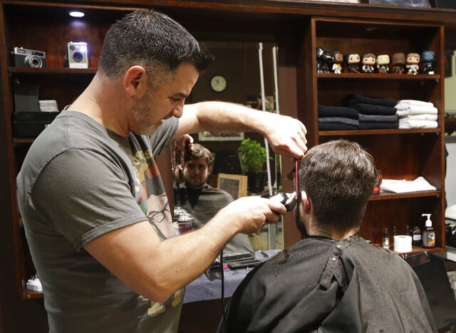 Cathedral Junction Barbers owner Conrad Fitz-Gerald cuts the hair of his son Heathcliff wait just past midnight in Christchurch, New Zealand, Thursday, May 14, 2020. New Zealand lifted most of its remaining lockdown restrictions from midnight Wednesday (noon Weds. GMT) as the country prepares for a new normal. Malls, retail stores and restaurants will reopen and many people will return to their workplaces. (AP Photo/Mark Baker)