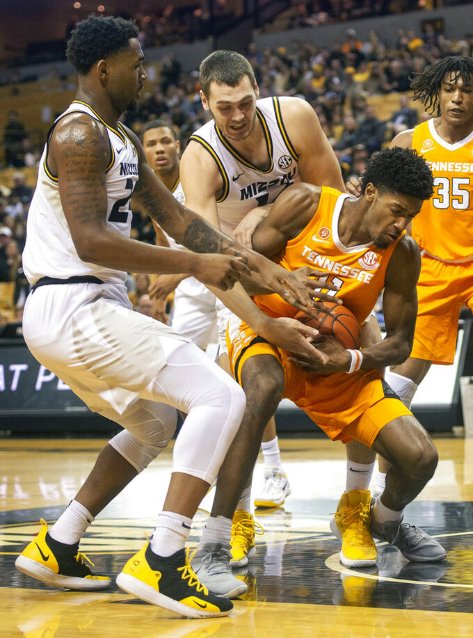 Tennessee's Kyle Alexander, right, pulls the ball away from Missouri's Kevin Puryear, left, and Reed Nikko, center, during the first half of an NCAA college basketball game Tuesday, Jan. 8, 2019, in Columbia, Mo. (AP Photo/L.G. Patterson)