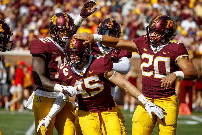 FILE - In this Sept. 15, 2018, file photo, Minnesota linebacker Carter Coughlin (45) celebrates his sack against Miami (Ohio) with Tai'yon Devers (12) and Julian Huff (20) in the first half of an NCAA football game, in Minneapolis. Coughlin was already a key player last season, starting every game and leading the team with 6½ sacks and 11½ tackles for loss, but he progressed to the role of a true game-changer for the Gophers up front. (AP Photo/Bruce Kluckhohn, File)