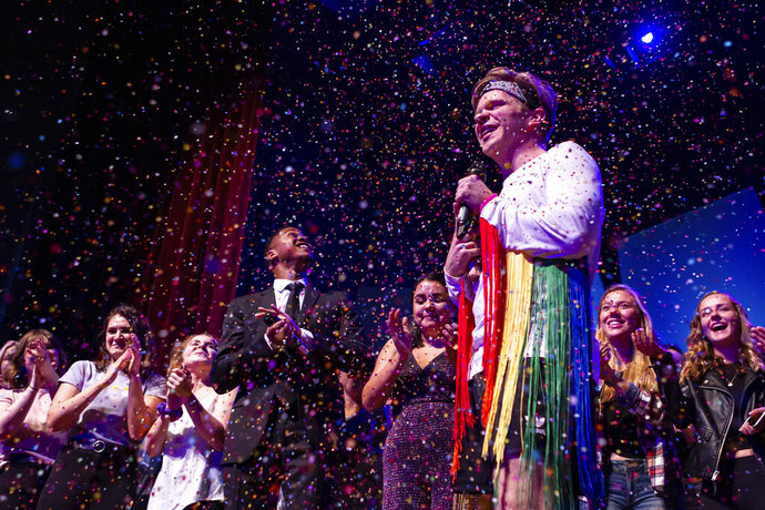 In this Saturday, Nov. 16, 2019 photo, Reid Arthur speaks as confetti falls at the ends of the lip sync competition at George Fox University in Newberg, Ore. Backup dancers pulled off his top layer to expose his revealing rainbow-colored streamers. (Jake Morgan/Religion News Service via AP)