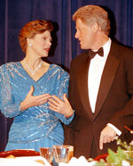 FILE - In this March 18, 1993, file photo, President Bill Clinton, right, speaks with Cokie Roberts, of ABC News, at the Radio and Television Correspondents Dinner in Washington. Roberts, the daughter of politicians who grew up to cover the family business in Washington for ABC News and NPR over several decades, died Tuesday, Sept. 17, 2019, in Washington of complications from breast cancer. She was 75. (AP Photo/Doug Mills, File)