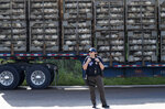 FILE - In this Aug. 7, 2019, file photo, a trailer loaded with chickens passes a federal agent outside a Koch Foods Inc., plant in Morton, Miss. Unauthorized workers are jailed or deported, while the managers and business owners who profit from their labor often aren't. Under President Donald Trump, the numbers of owners and managers facing criminal charges for employing unauthorized workers have stayed almost the same. (AP Photo/Rogelio V. Solis, File)