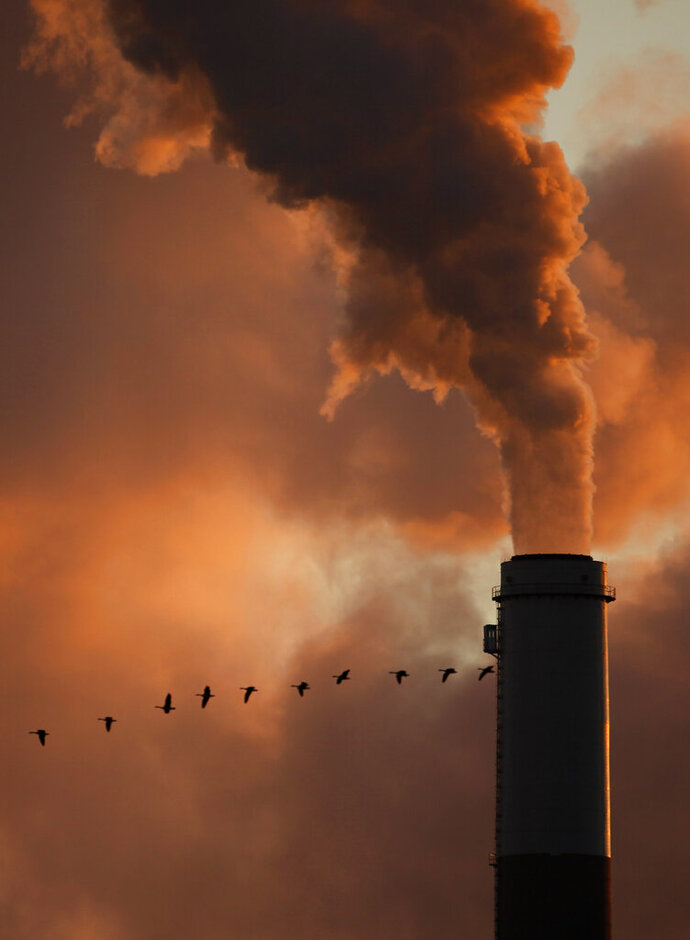 FILE - The Jan. 10, 2009 file photo shows a flock of geese flying past a smokestack at the Jeffery Energy Center coal power plant near Emmitt, Kan. A new study says the amount of global warming already baked into the air because of past carbon pollution is enough to blow past internationally agreed upon climate limits. A study on Monday, Jan. 4, 2021 takes a different look at what's called committed warming that comes from heat-trapping gases staying in the atmosphere for more than a century. (AP Photo/Charlie Riedel, File)