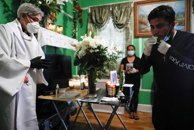 Family members receive communion by their own hand as the Rev. Fabian Arias, left, performs an in-home service beside the remains of Raul Luis Lopez who died from COVID-19 the previous month, Saturday, May 9, 2020, in the Corona neighborhood of the Queens borough of New York. (AP Photo/John Minchillo)