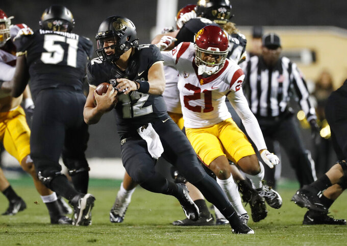 Colorado quarterback Steven Montez, left, avoids Southern California safety Isaiah Pola-Mao during the first half of an NCAA college football game Friday, Oct. 25, 2019, in Boulder, Colo. (AP Photo/David Zalubowski)