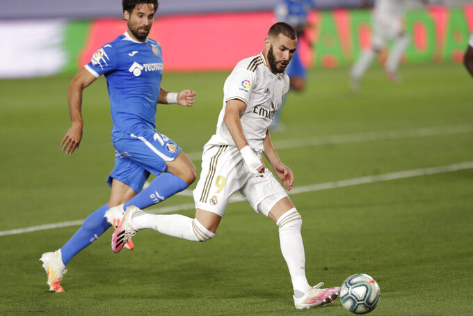 Real Madrid's Karim Benzema, right, is challenged by Getafe's Xabier Etxeita during the Spanish La Liga soccer match between Real Madrid and Getafe at the Alfredo di Stefano stadium in Madrid, Spain, Thursday, July 2, 2020. (AP Photo/Bernat Armangue)